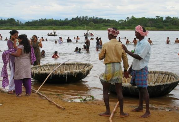 Échange fraternel entre meneurs de coracle (bateau-panier) au bord d'une rive de laCauvery,Karnataka, Inde